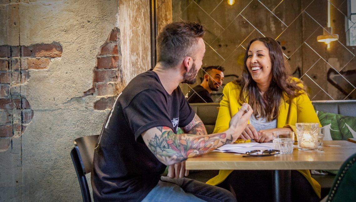 man en vrouw lachen aan tafel